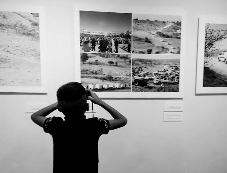 הקול שמאחורי התמונה – ילד מצלם את המיצגים בפתיחת התערוכה